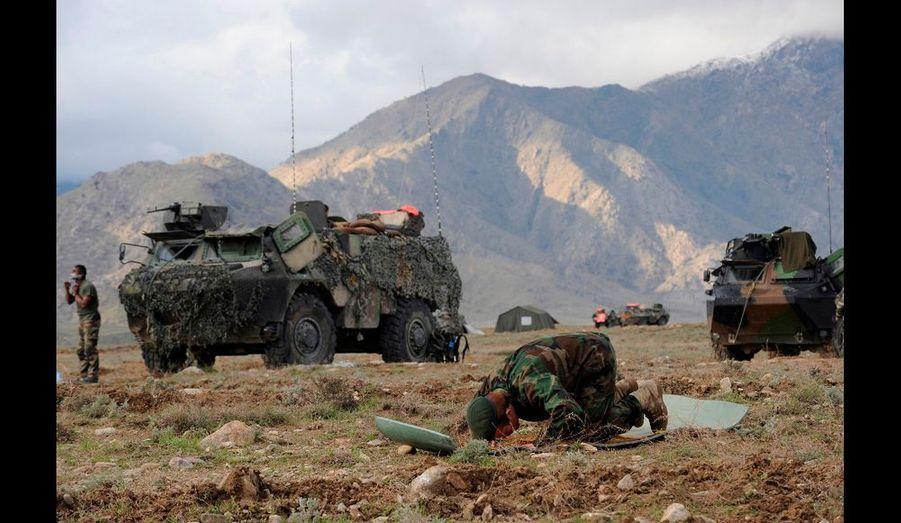 3ème jour de l'Opération NIZAMI, les travaux de construction de la FOB continuent malgré les intempéries.Un soldat afghan fait sa prière sur fond de VAB (véhicule de l'avant blindé) français.