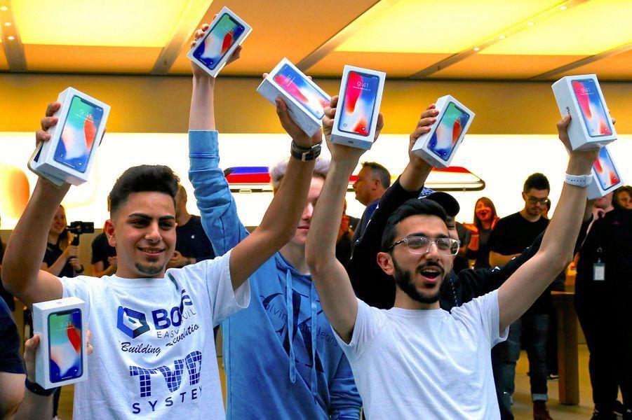 Victorieux, deux des premiers clients de cet Apple Store de Sydney, en Australie, brandissent leurs iPhone X, vendredi.