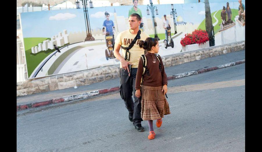 Les colons juifs installés dans les quartiers arabes sont, comme cette jeune fille qui rentre de l'école, escortés par des gardes armés de la sécurité privée de l'association Elad.