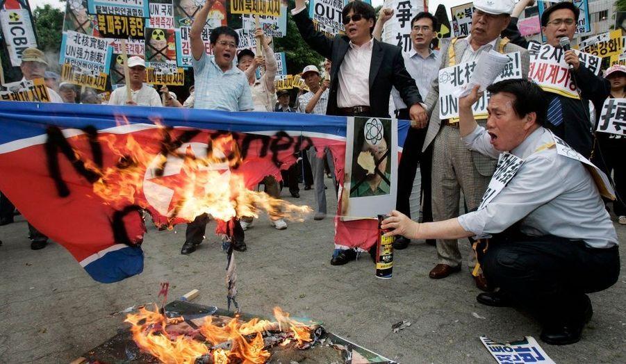 Des protestants sud-coréens brûlent en pleine rue le drapeau de la Corée du nord et des portraits de Kim Jong-il.