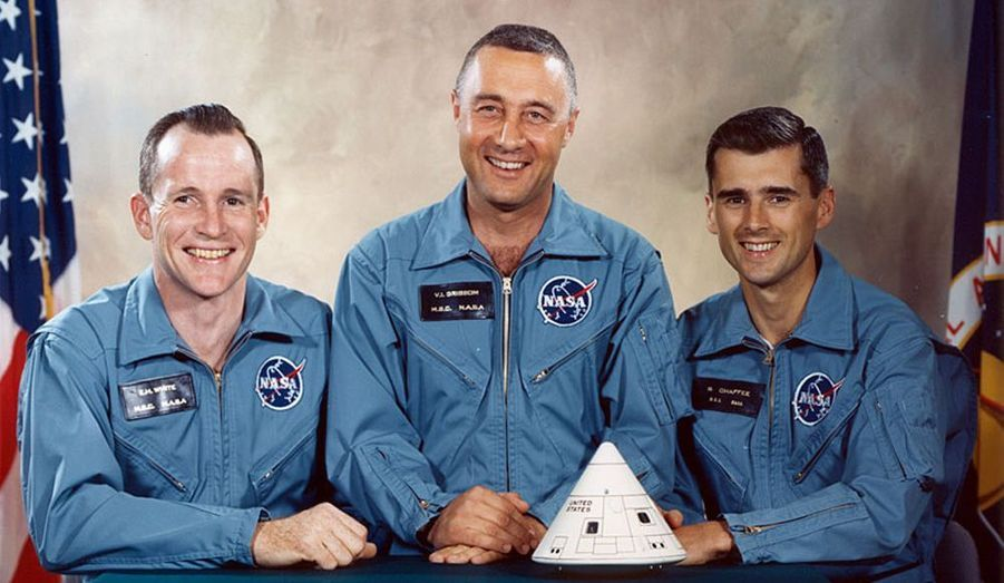 Souriants, Ed White, Gus Grissom et Roger Chaffee (de g. à dr.) posent devant la maquette de la capsule qui va causer leur perte.