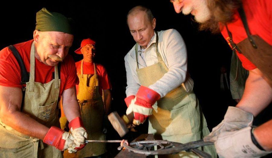 """Vladimir Poutine bat le fer quand il est chaud , lors d'une visite au """"Talsy"""", le musée d'Architecture et d'Ethnographie de la région d'Irkutsk, en Sibérie de l'est, en 2009."""