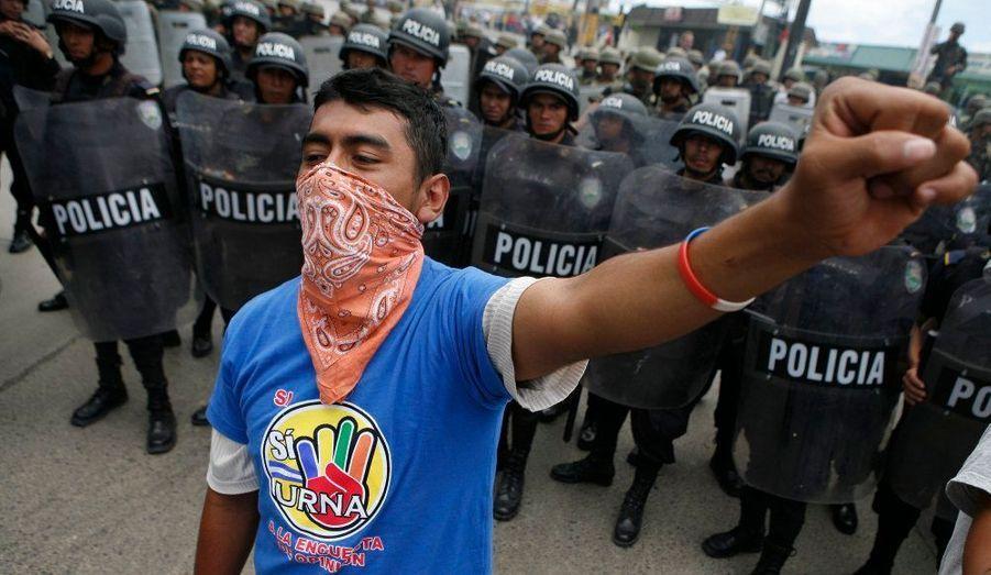 Un partisan du président déchu Zelaya, entouré d'un impressionnant escadron de police, chante l'hymne national du Honduras sur le tarmac de l'aéroport de Tegucigalpa.