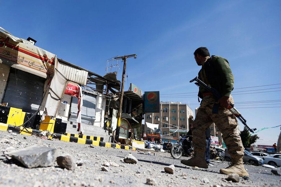 Un combattant chiite devant un magasin ravagé à côté du palais présidentiel de Sanaa