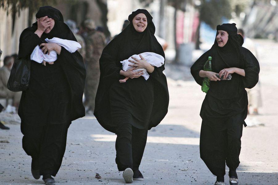 Le 12 août. Ces femmes,avec leurs nouveau-nés, laissent éclater leur joie après la libération de leur quartier.