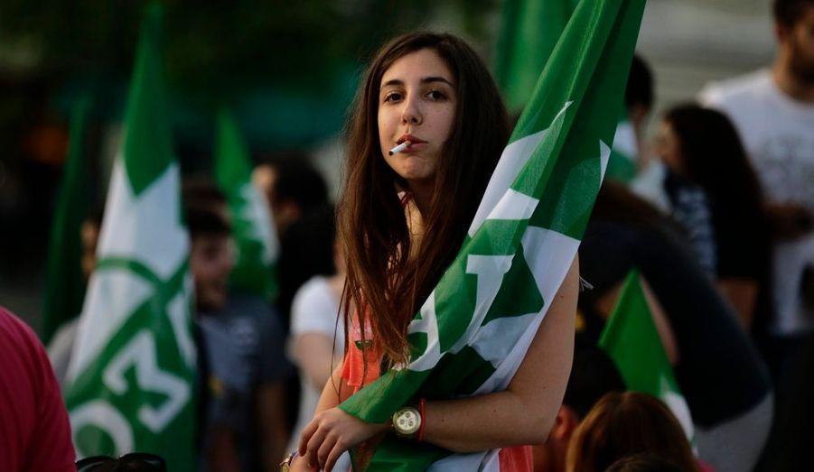Une fille fume une cigarette avant l'arrivée duchef du parti socialiste grecPasok Evangelos Venizelos,lors d'un rassemblement à Athènes, la veille des élections législatives dans le pays.