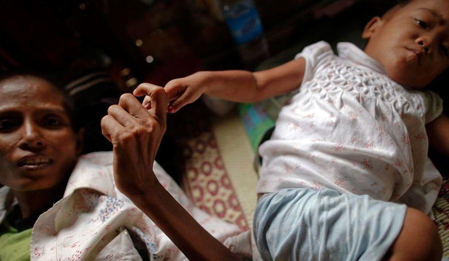 Ma Jam, 42 ans, atteinte du Sida, tient la main de son fils de deux ans qui a contracté le virus, dans un hospice créé par un membre de la Ligue nationale pour la démocratie (LND),dans la banlieue de Rangoon.