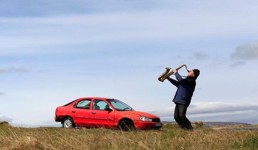 L'artiste et poète Barry Edgar Pilcher, 69 ans, pose jouant du saxophone sur l'île d'Inishfree. Pilcher est le seul habitant de cette île d'Irlande où il vit depuis 20 ans, et qu'il ne quitte qu'une fois par semaine pour chercher sa pension et faire ses courses.