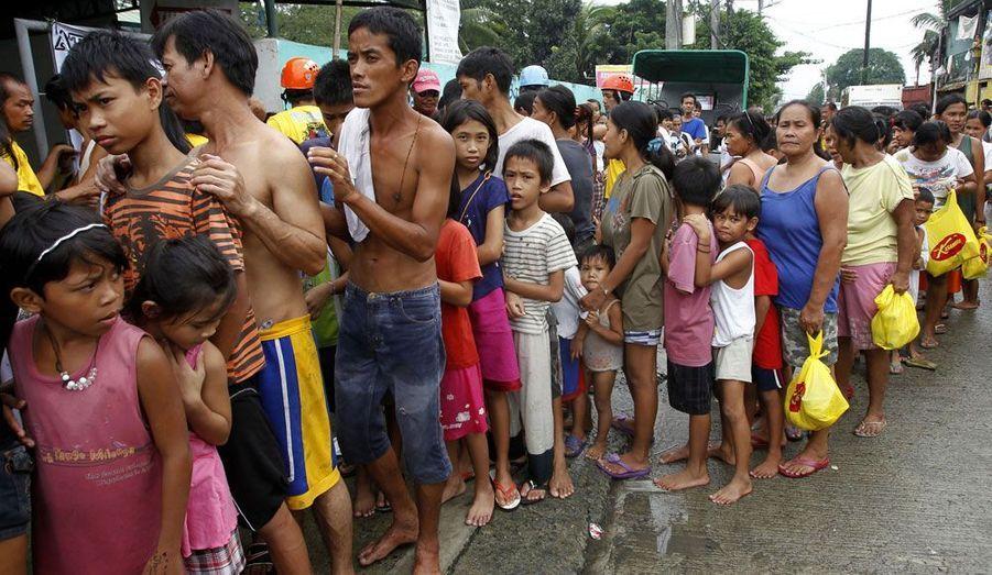 Les victimes des inondations font la queue pour obtenir de la nourriture.