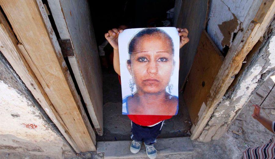 """Kevin Alberto, deux ans, tient le portrait de sa mère Maricela Gonzalez, introuvable depuis mai 2011 comme 900 autres femmes tuées ou disparues ces vingt dernières années. Car Ciudad Juarez est le théâtre d'un véritable massacre de femmes entamé en 1993. Une infime minorité de ces assassinats et de ces enlèvements ont été élucidés. Malgré une mobilisation internationale d'ONG, d'intellectuels, de journalistes, d'artistes et d'écrivains, ce """"gynécide"""", du néologisme créé par Antoinette Fouque, se poursuit sous les yeux impuissants -ou complices- de la police et de la justice. (A voir ce webdocumentaire sur www.lacitedesmortes.net)"""