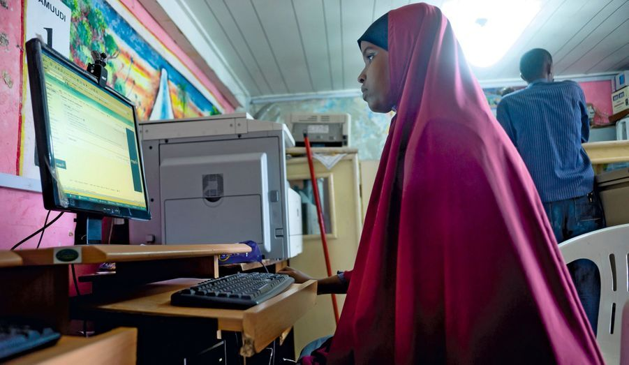 Le regard concentré sous son voile, une jeune femme travaille sur écran au cybercafé Caaminou, un nouveau local aux normes quasi occidentales.