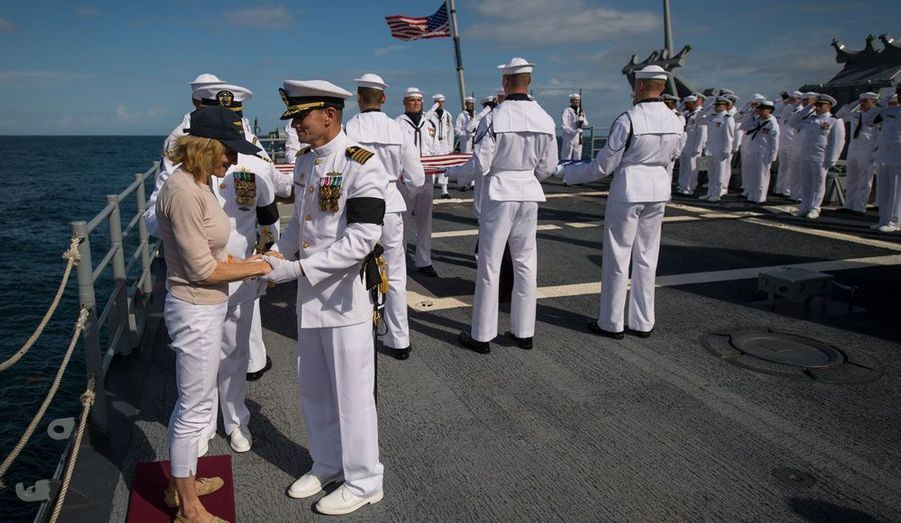 Le capitaine du bateau, Steve Shinego, réconforte Carol Armstrong, la femme de l'astronaute après qu'elle a dispersé les cendres de son mari dans la mer.