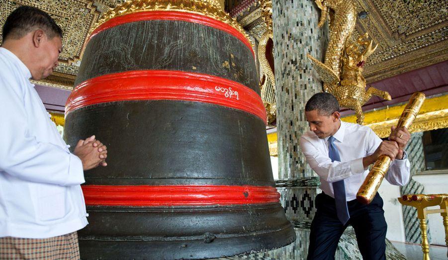 En visite officielle en Birmanie, le Président s'apprête à faire résonner la cloche de la pagode de Shwedagon.