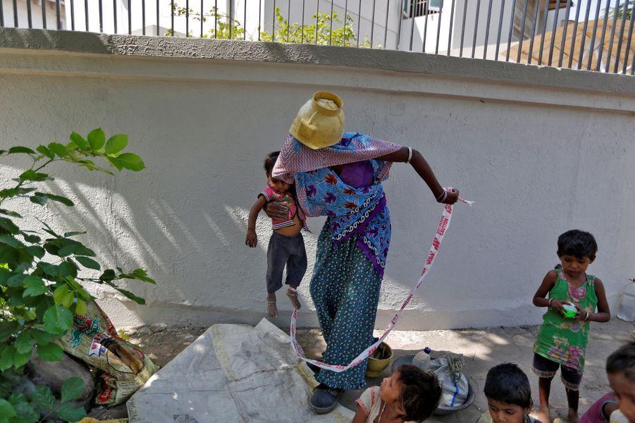 A Ahmedabad, en Inde, la petite Shivani passe ses journées attachée à une pierre pendant que ses parents travaillent.