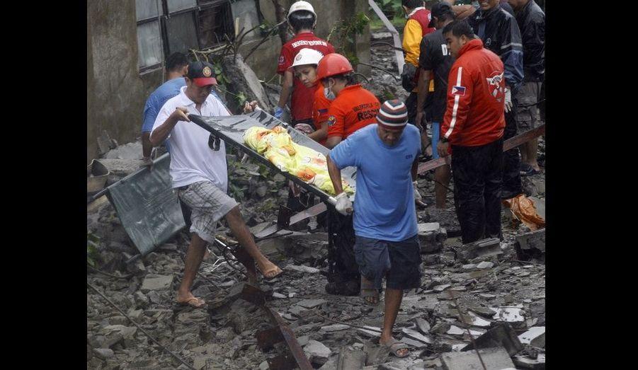 Des sauveteurs dégagent un corps des décombres d'une maison à Valenzuela. Les vents violents ont abattu une cloison, tuant quatre habitants.