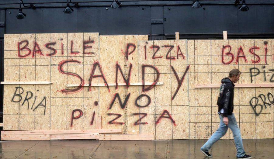 """Un homme passe devant une pizzeria d'Hoboken, dans le New Jersey, qui prévient d'éventuels clients: """"Pas de pizza"""" à cause de Sandy."""