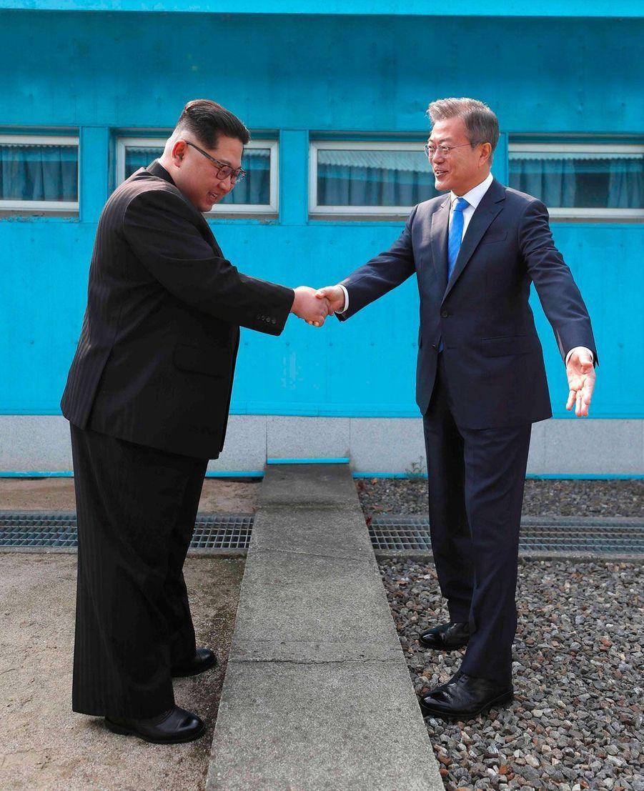 Poignée de main entre Kim Jong-un et Moon Jae-in au dessus de la ligne de démarcation séparant les deux Corées.