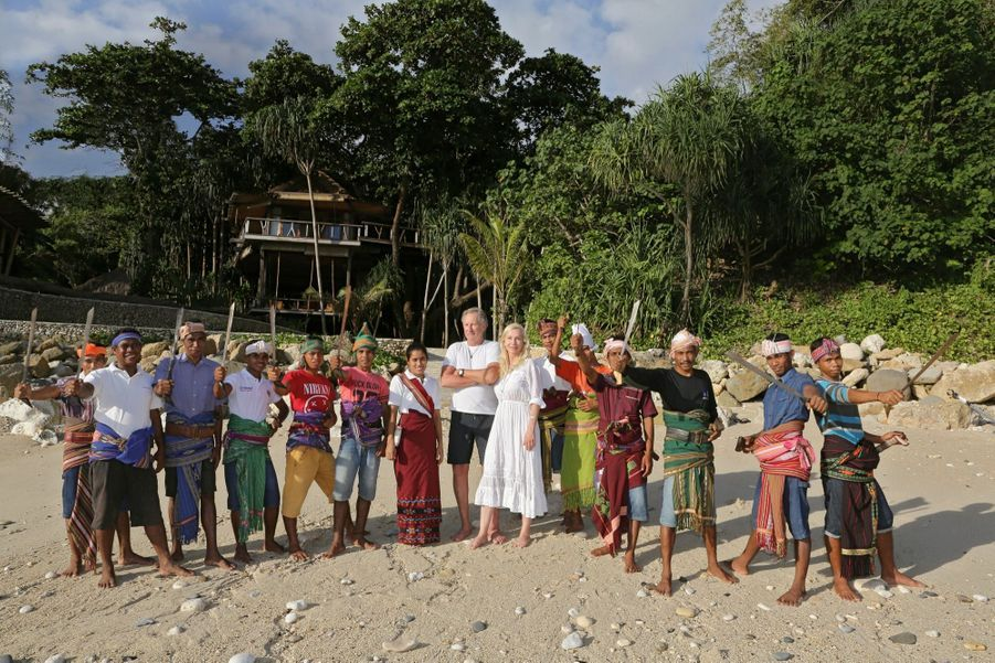 Claude, 68 ans, et Petra, 55 ans, devant le bungalow Tree House,avec des employés qui brandissent leur arme traditionnelle, le parang.