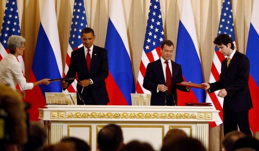 Barack Obama et Dmitri Medvedev donnent à leurs assistants les accords qu'ils viennent de signer sur les armes nucléaires.