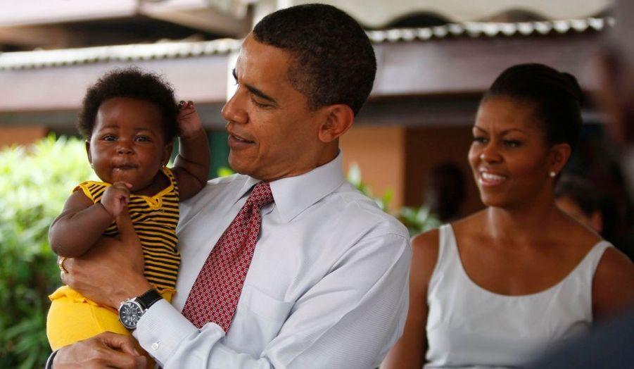 Barack Obama prend un bébé dans ses bras lors de sa visite de l'hôpital Ghanéen d'Accra.