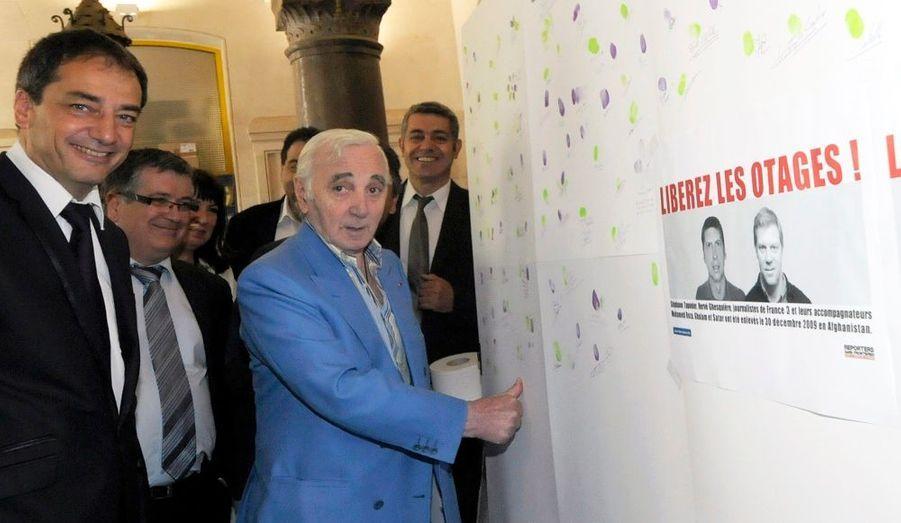 En marge de son passage à la mairie de Valence, Charles Aznavour a laissé l'empreinte de son pouce et sa signature pour soutenir les otages français, initiative prise par la ville et le Club de la Presse Drome/Ardeche.