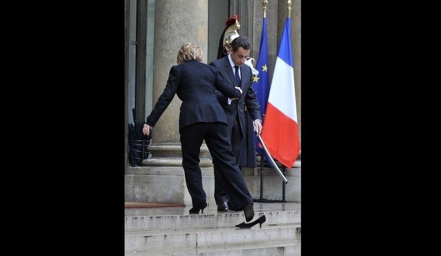 Accueillie par le président de Nicolas Sarkozy, la secrétaire d'Etat, Hilary Clinton, perd sa chaussure en montant les marches de l'Elysée.