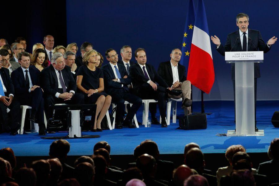 Francois Fillon s'exprime sur scène, avec ses principaux soutiens derrière lui.