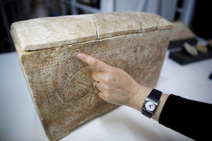 Une archéologue pointe du doigt un ossuaire sur lequel se trouve des inscriptions en hébreux.