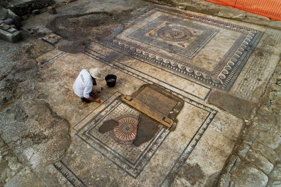 Le pavement de la salle mosaïquée en cours de nettoyage.