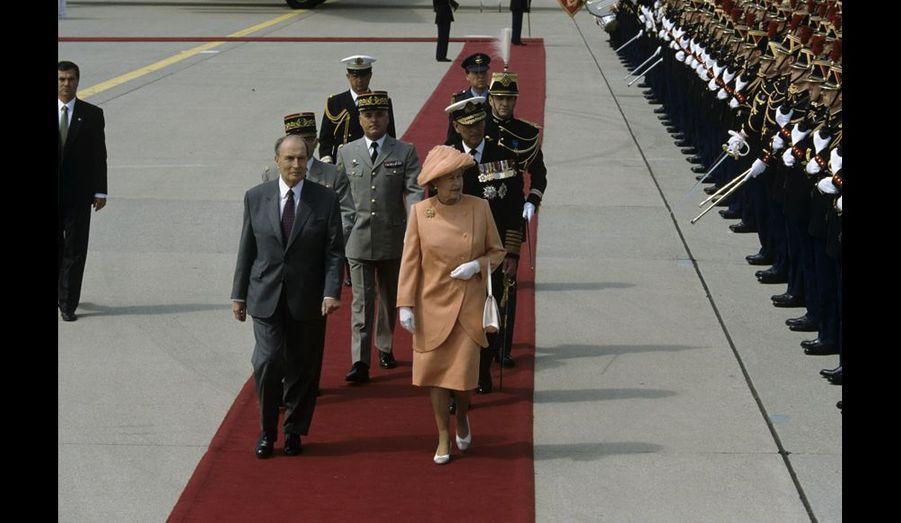 La reine d'Angleterre et le président François Mitterrand passent en revue la Garde républicaine en tenue d'apparat à l'aéroport Paris-Orly, sous le soleil du printemps.