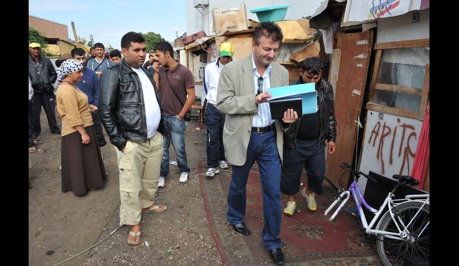 Le commissaire de police roumain poursuit son recensement, suivi par une vingtaine d'habitants inquiets.