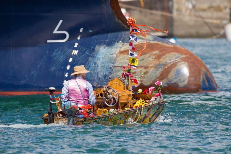 «Music Boat», skippé par Reinier Sijpkens, croise le bulbe d'étrave d'un géant des mers. Comme son nom l'indique, cette minicoque de noix, fleurie comme un quai d'Amsterdam, est une boîte à musique flottante.