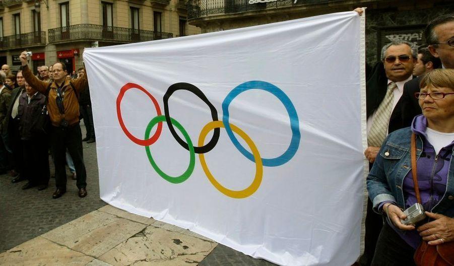 Des gens brandissant le drapeau olympique en hommage à ce passionné de sport.