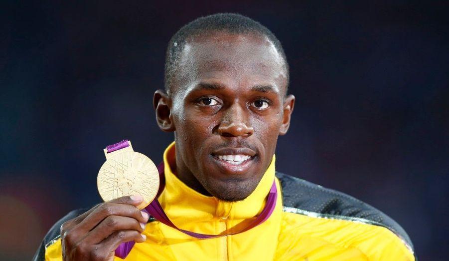Le Jamaïcain Usain Bolt prend la pose avec sa médaille d'or du 100 mètres après la cérémonie protocolaire.