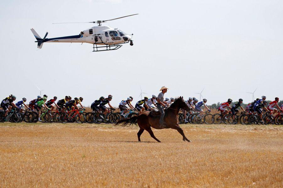 Un homme à cheval suit les coureurs lors de la sixième étape le 6 juillet.