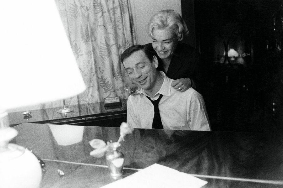 Simone Signoret auprès de son mari Yves Montand qui joue du piano, chez eux à