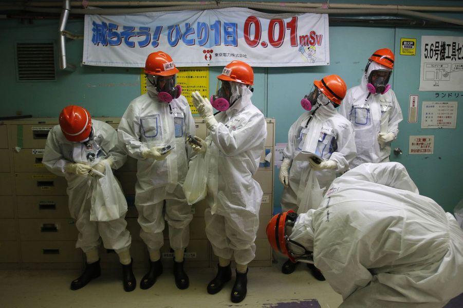 """Des membres des médias accompagnés d'employés de Tokyo Electric Power Co. sont entrés lundi dans la centrale nucléaire de Fukushima. Ils se tiennent près d'une banderole où l'on peut lire: """"Diminution de 0,01 mSv par jour pour une personne""""."""