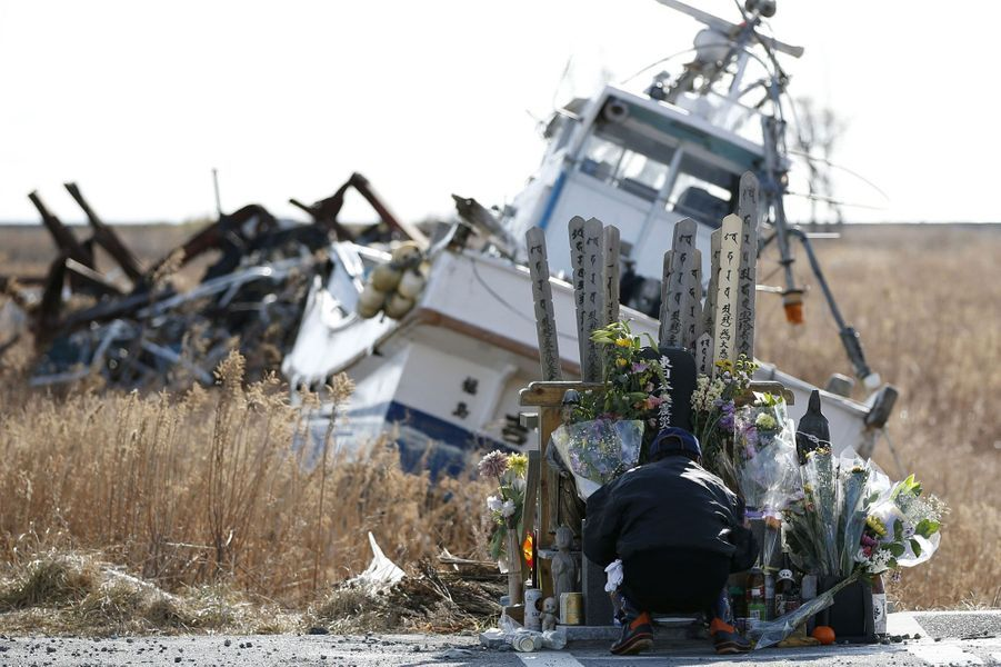 Ce mardi, un homme dépose des fleurs en l'honneur des victimes du tremblement de terre et du tsunami, dans la préfecture de Fukushima.