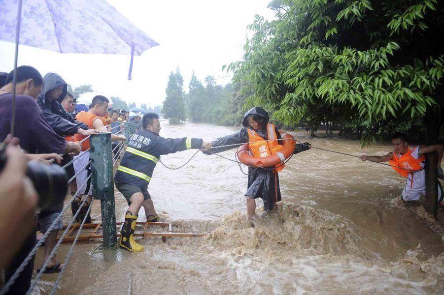 Pluies torrentielles, glissements de terrains et inondations. Depuis le 7 juillet, la Chine est en proie au déluge. Des intempéries qui ont touché plus particulièrement la province du Sichuan, au sud-ouest du pays. Près de 70 personnes sont mortes et 179 sont portées disparues. D'autres provinces sont également touchées et endeuillées. Sur la photo, les secouristes s'aident d'une corde pour que les habitants de Dujiangyan,dans la province du Sichuan, échappent aux flots.