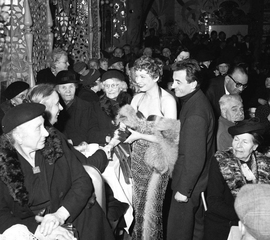Jacqueline Francois et Charles Aznavour distribuent du chocolat aux personnes âgées, en 1955.
