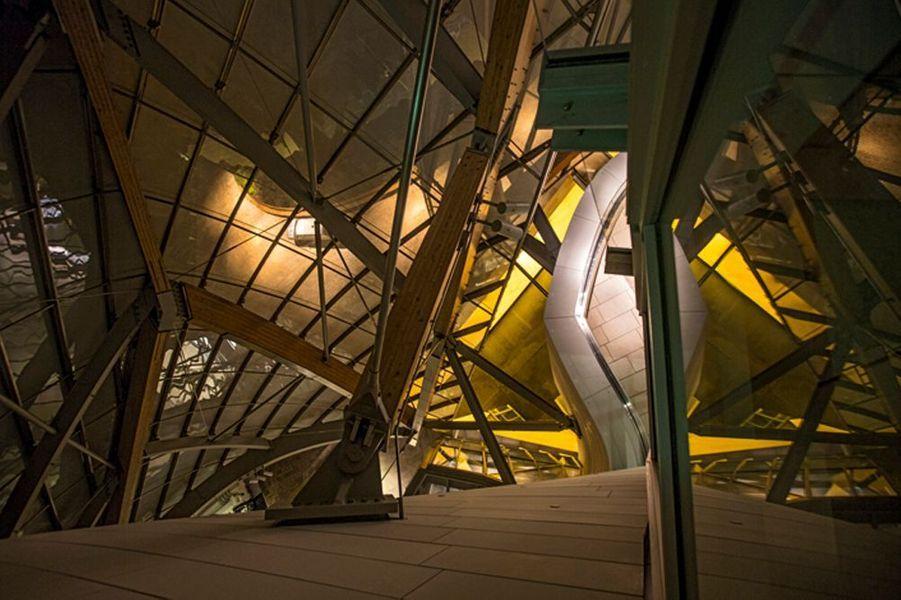 Vue plongeante depuis une terrasse. Les voiles de verre qui recouvrent la structure sont soutenues par une arche en acier et des poutres de bois.