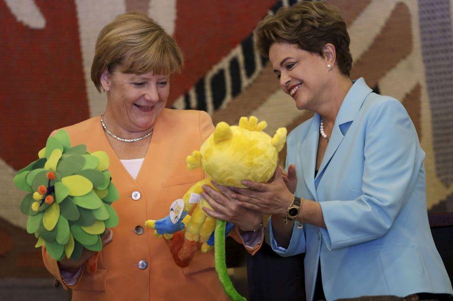 Angela Merkel et son hôte Dilma Rousseff s'amusent devant les peluches des mascottes des Jeux de Rio 2016.Vinicius - celle dans les mains de la leader brésilienne - représente les Jeux olympiques, Tom, la seconde, les Paralympiques.