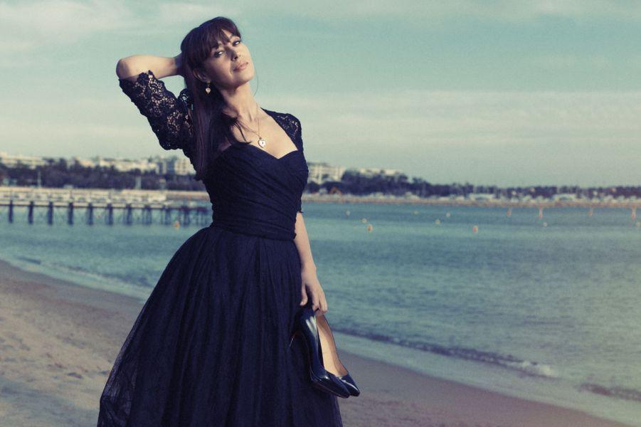 En mai 2014, Monica Bellucci pose en robe-bustier de dentelle noire Dolce & Gabbana, sur la plage de l'hôtel Martinez