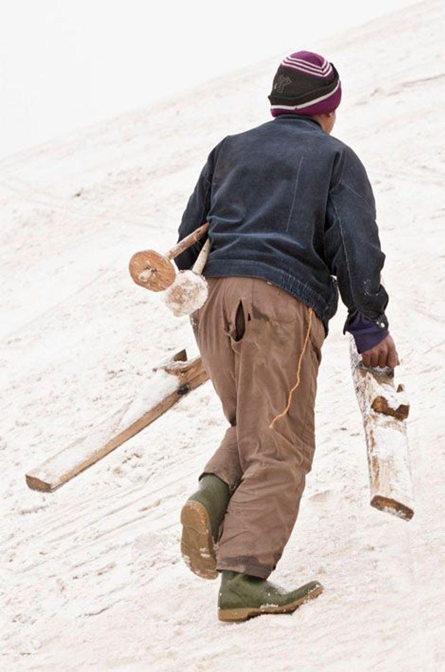 Sayed Ali prend ses bâtons sous le bras et les skis à la main. Au sommet, il bricole une ficelle qui servira de fixation.