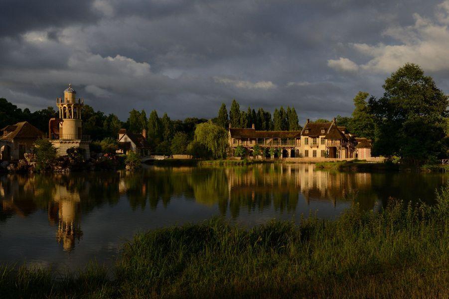 Sur la rive de l'étang artifciel et dans la lumière du soir, la maison de la Reine est composée de deux bâtiments reliés par une galerie. A gauche, la tour de Marlborough entourée de la laiterie de propreté et (à droite) du colombier.Un décor bucolique pour une souveraine éprise de comédies champêtres. Pour la jouer « paysanne », Sa Majesté a commandé un ensemble de chaumières normandes. Une résidence secondaire dans le parc duPetit Trianon, à quelques centaines de mètres du château de Versailles mais à des années-lumière de son étiquette. Entre champs et potagers,vaches et poules, Marie-Antoinette respire le bon air de la liberté. Son refuge, qu'elle avait voulu sans extravagance se révéla plus qu'une fantaisie, une vraie folie… condamnée à une mort lente après celle de sa propriétaire. Grâce au mécénat deDior, le corps principal du hameau, la maison de la Reine, va retrouver vie. Comme autrefois.A lire aussi: La restauration du hameau de la reineSurtout, que cela fasse vrai, simple et campagnard ! Les douze bâtiments, l'étang, le ruisseau : tout a été créé pour l'occasion… et aux frais du peuple. Les toits sont en chaume, les murs en crépi, mais ils abritent des intérieurs luxueux et raffinés. Cinq demeures sont réservées à la rurale souveraine, les autres à la vie de la ferme. Construit sans fondation sur des marais, le village n'était pas fait pour survivre à sa reine. Il est peu à peu restauré à l'identique. Seule entorse à la reconstitution de la maison de la Reine, le mobilier. Ce ne sera pas celui de Marie-Antoinette, dispersé pendant la Révolution, mais les meubles de l'impératrice MarieLouise : Napoléon Ier, déjà, avait partiellement remis en état le hameau pour sa seconde épouse.