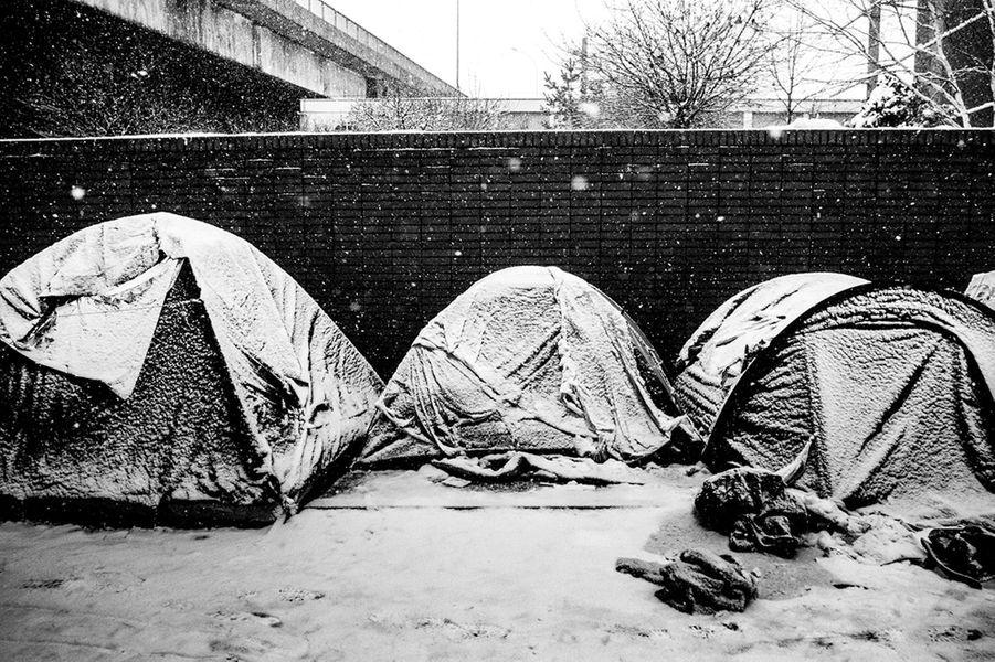 Des tentes immaculées de blanc par la neige qui tombe. Le centre humanitaire étant complet, les personnes sont obliges de dormir dans la rue. 8 février 2018. Paris. France.