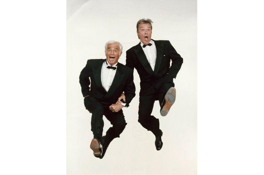 """1997 - Depuis 40 ans ils sont les as des as du cinéma français. Jean-Paul Belmondo et Alain Delon, les rois de cœur du grand public. Mais pour les 50 ans du festival de Cannes, la Croisette en fêteoublie de les inviter. Il y a de quoi rugir! Mais les deux lions préfèrent montrer que en plus de la cote d'amour, ils ont le sens de l'humour. Comme deux gosses ! Heureux de faire un pied de nez au festival ils montrent qu'après 40 ans de carrière ils ont toujours du ressort. La photo fera la couverture de Match et le titre sera """"Cannes, on n'en a rien à cirer""""."""