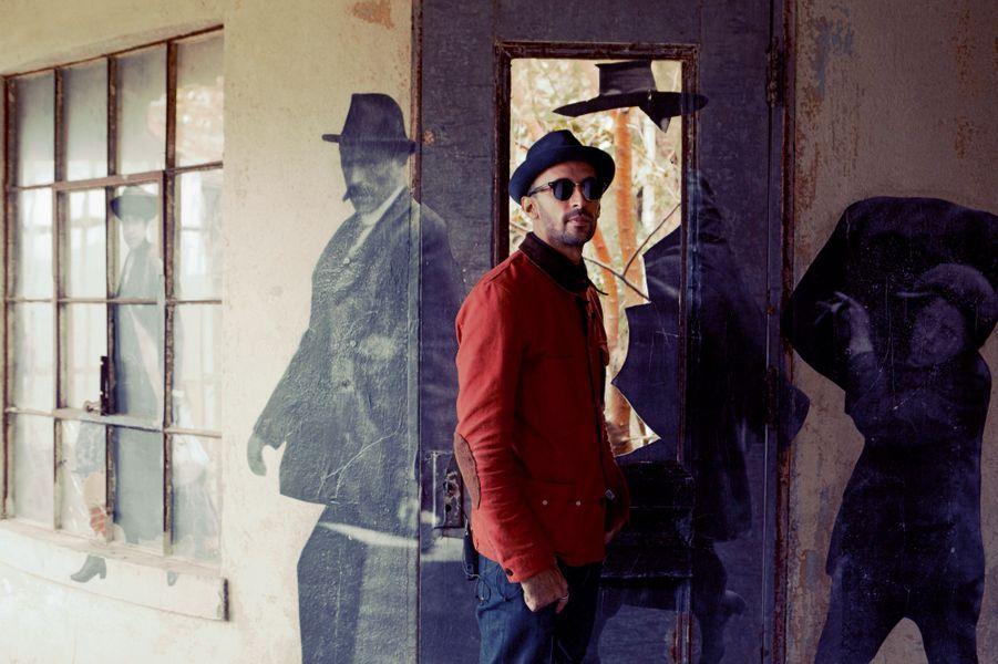 Dans l'aile sud de l'hôpital, toujours avec son chapeau et ses lunettes noires, JR, le 16 octobre 2014. Aux âmes errantes, un artiste qui n'oublie pas... Sur les parois désolées de l'hôpital d'Ellis Islandfermé depuis soixante ans, le «photograffeur» ouvrela galerie de portraits des oubliés. Au début du XXesiècle, ils étaient 12millions à gagner l'Amérique pour forcer le destin. Mais pas de ticket pour l'espoir sans examen sanitaire… Plus d'unmillion d'entre eux ont commencé le voyage entre ces murs et quelques milliers l'ont fini au «pavillon des fous» ou dans la salle d'autopsie. Les 25 photographies géantes ne dissipent pas le mystère qui, comme une nappe de brouillard, enveloppe «l'île des larmes». L'Histoire ne se livre pas, ditJR. Il faut faire un pas vers elle. Son exposition «Unframed» aide à le franchir. Les visites (sur rendez-vous) affichent complet jusqu'en mars 2015.C'est un parcours jonché de tristesse et de dignité. Une porte, un escalier, des fenêtres délabrées, des meubles rongés servent de toile de fond à des tableaux sans cadre… Et soudain la magie prend forme. Des fantômes surgissent derrière les regards qui se lézardent avec les murs, dans ces visages d'enfants morcelés par le verre cassé. Le temps ne change rien au malheur. Dans certaines parties de l'hôpital, «trop chargées», comme la salle de dissection, JR n'a pas réussi à choisir une affiche. Là où la réalité étouffe la création, le «serial-colleur» s'est résolu à l'abstinence.