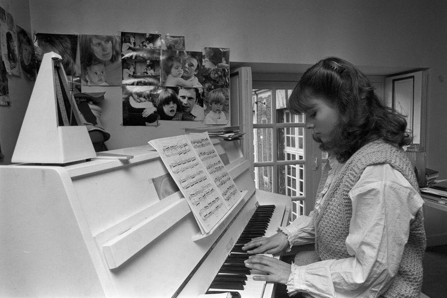 Marie Trintignant étudiant le piano, au mur des photos d'elle avec ses parents Nadine et Jean-Louis Trintignant et des photos de son petit frère Vincent. Photo prise en 1978.