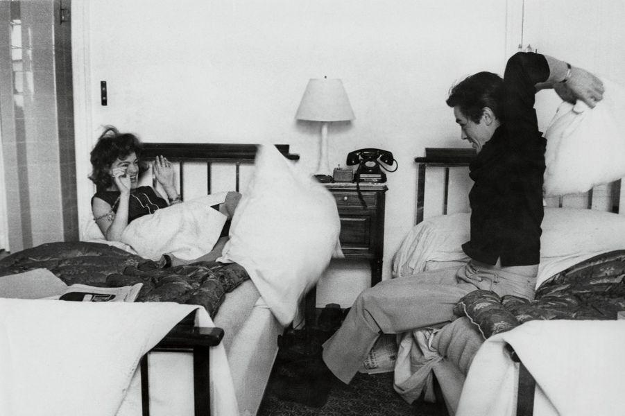 Romy SCHNEIDER et Alain DELON faisant une bataille de polochons, assis sur des lits jumeaux dans une chambre à Paris au début des années 60.